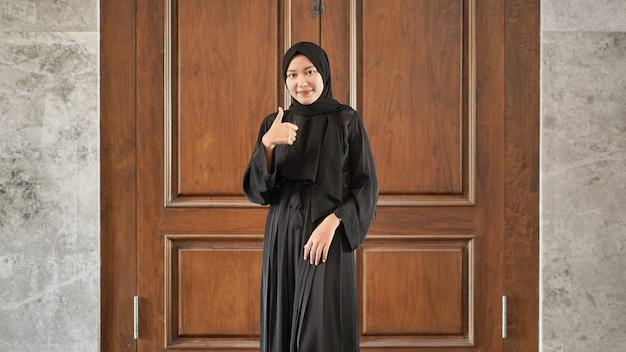 Mujer en vestido negro musulmán gesticulando bien en la puerta