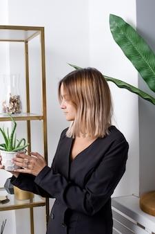 Mujer en vestido negro con plantas verdes