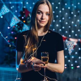 Mujer en vestido de noche con copa de vino espumoso celebración año nuevo