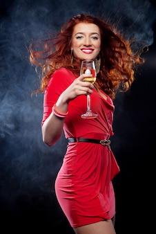 Mujer en vestido de noche con copa de vino espumoso