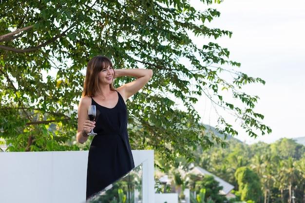 Mujer en vestido de noche negro con copa de vino en el balcón tropical