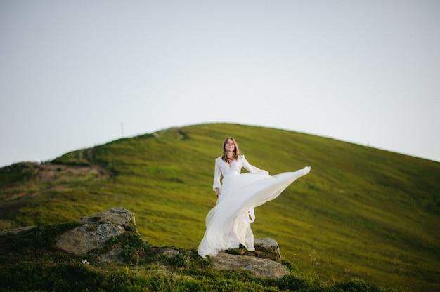 Mujer en un vestido de novia corre por el campo hacia las montañas