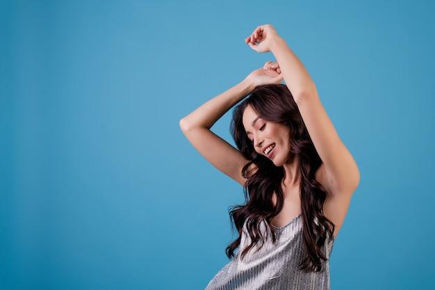 Mujer en vestido plateado bailando y sonriendo aislado sobre azul