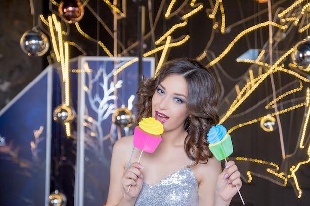 Mujer con vestido plateado brillante está sosteniendo cupcake de fiesta en el palo, cabina de fotos de fiesta