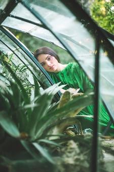 Mujer en vestido posando en una casa verde