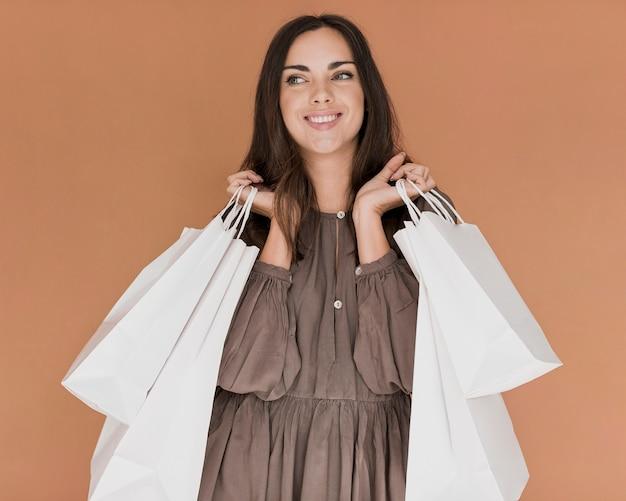Mujer con vestido y redes de compra en ambas manos.