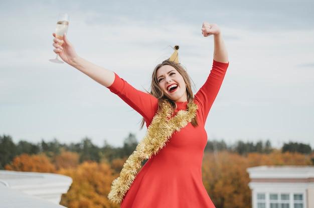 Mujer en vestido rojo bailando en la azotea