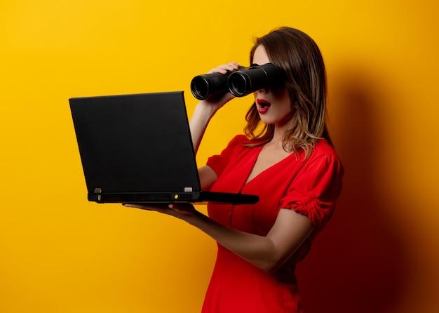 Mujer en vestido rojo con binoculares y computadora portátil