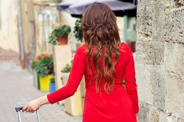 Mujer en vestido rojo camina con maleta en la calle de la ciudad.