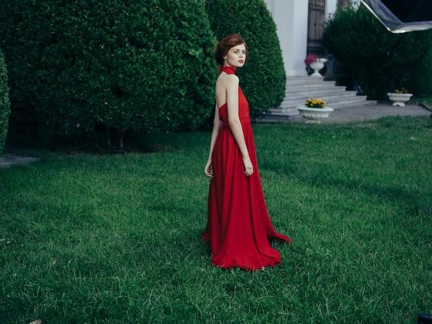Mujer en vestido rojo de lujo caminar al aire libre mascarada estilo gótico