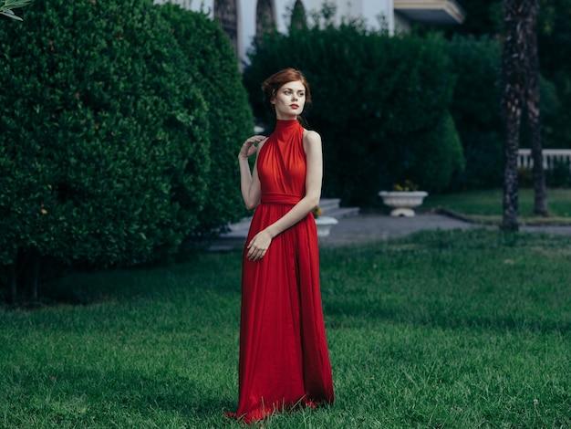Mujer en vestido rojo de lujo princesa mascarada encanto hojas verdes.