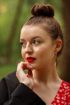 Mujer de vestido rojo con maquillaje de verano sobre fondo verde sonrisas