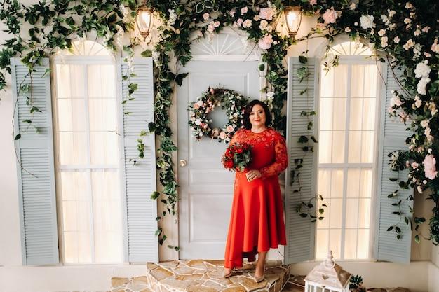 Una mujer con un vestido rojo está parado y sostiene un ramo de rosas rojas y fresas