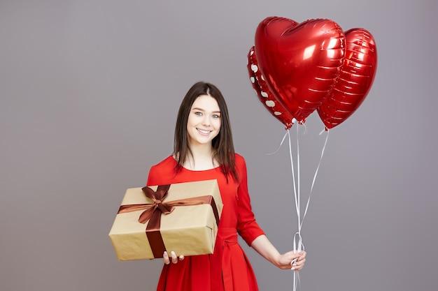 Una mujer con un vestido rojo sobre una pared gris tiene globos y una caja de regalo en sus manos