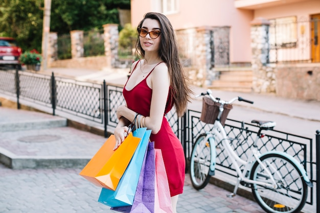 Mujer en vestido rojo sosteniendo bolsas de papel