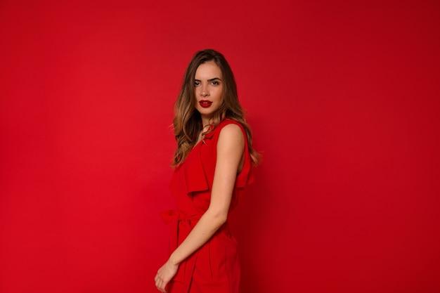 Mujer en vestido rojo de vacaciones con labios rojos posando
