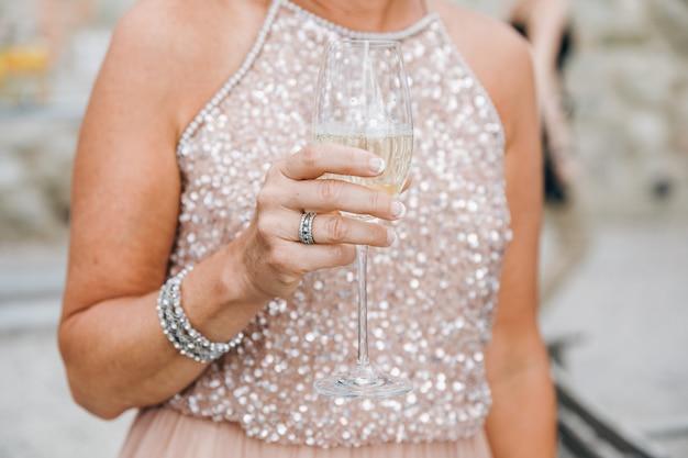 La mujer en vestido rosado chispeante sostiene el vidrio de champán en su ar