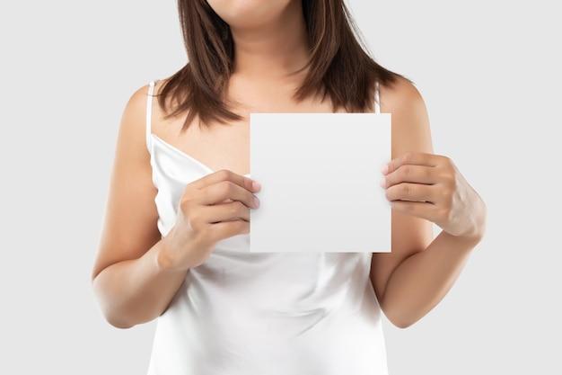 Una mujer en vestido de satén blanco sosteniendo un papel en blanco blanco sobre gris