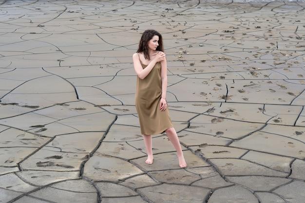 Una mujer con un vestido en el suelo agrietado.