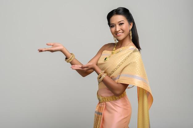 Mujer con vestido tailandés que hizo un símbolo de mano