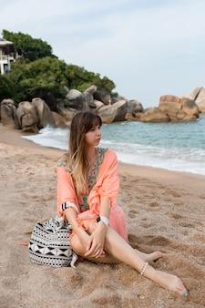 Mujer en vestido de verano boho sentado en la arena cerca del mar. estado de ánimo tropical.