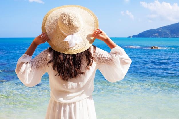 Mujer en vestido de verano con sombrero de paja