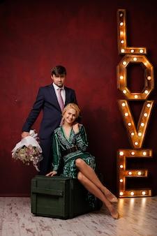 Mujer en el vestido verde sentada en la caja con su hombre