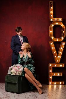 Mujer en el vestido verde con su hombre en el fondo título de luz amor