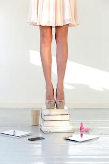 Mujer con vestido y zapatos en libros apilados