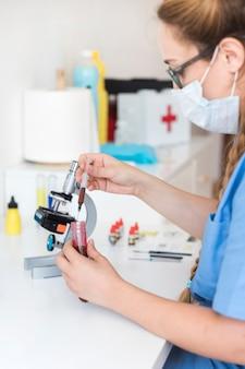 Mujer veterinaria examinando muestra de sangre en clínica