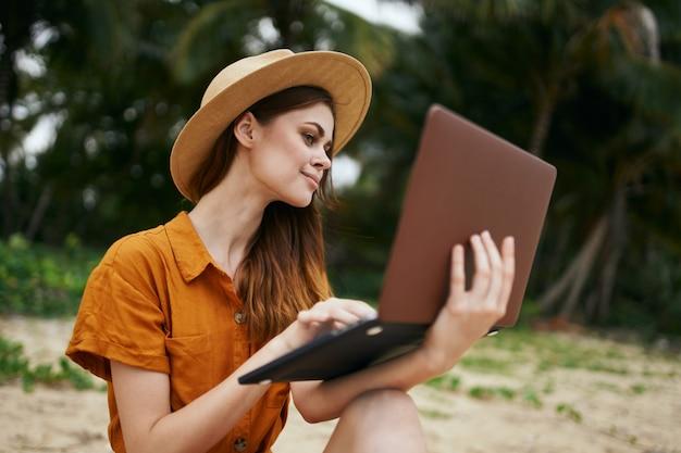 Una mujer viaja con una computadora portátil a lo largo del océano a lo largo de la arena con palmeras