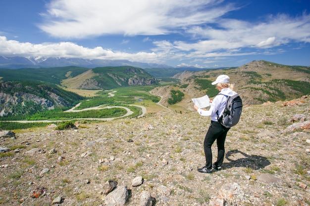 Mujer viaja en las montañas. mujer de senderismo utilizando un mapa. excursionista mujer leyendo el mapa en las montañas.