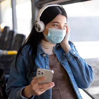 Mujer viajando con máscara y auriculares