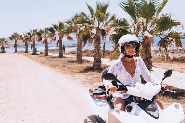 Mujer viajando en quad por el océano
