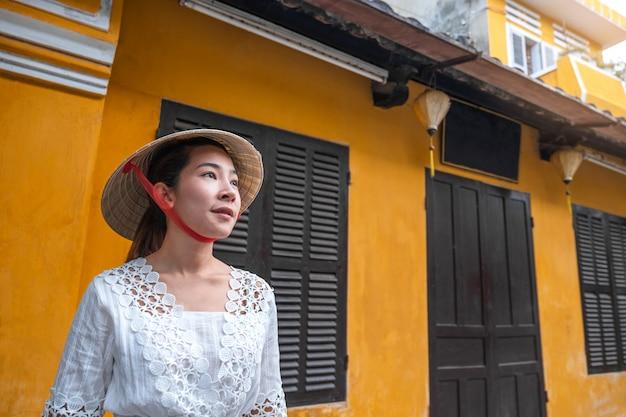 Mujer de viaje en las calles de hoi an, vietnam