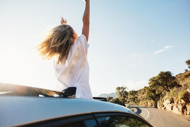 Mujer en viaje por carretera en coche saludando por la ventana sonriendo.