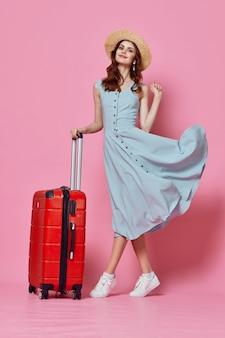 Mujer de viaje de moda con maleta roja en vestido azul