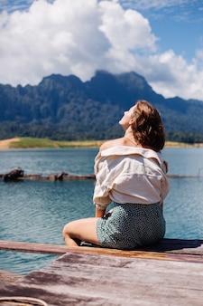 Mujer en viaje turístico de vestido y chaqueta de verano en tailandia, parque nacional de khao sok, vista increíble en barcos y lago.