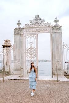 Mujer de viaje con vista del palacio de dolmabahce estambul paisaje urbano flotante barcos turísticos en el bósforo, estambul