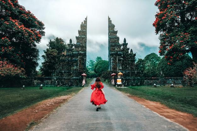 Mujer viajera corriendo en las puertas del templo hindú de bali, indonesia