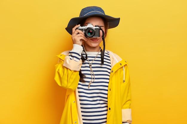 Mujer viajera hace fotos memorables durante el viaje, sostiene una cámara retro, toma imágenes de un hermoso paisaje o lugar, vestida con un jersey de rayas, un impermeable y un sombrero, aislado sobre una pared amarilla