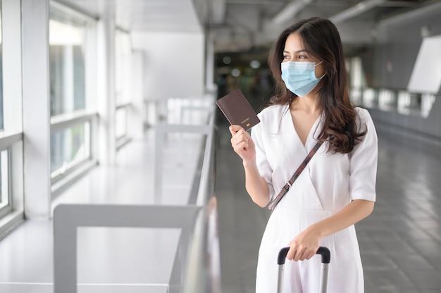 Una mujer viajera lleva una máscara protectora en el aeropuerto internacional, viaja bajo la pandemia de covid-19,