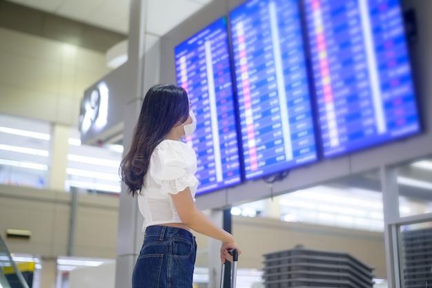 Una mujer viajera lleva una máscara protectora en el aeropuerto internacional, viaja bajo la pandemia de covid-19