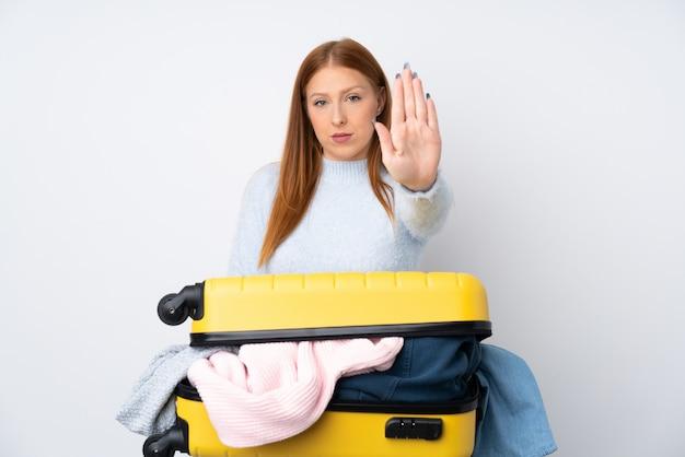 Mujer viajera con una maleta llena de ropa haciendo gesto de parada con la mano