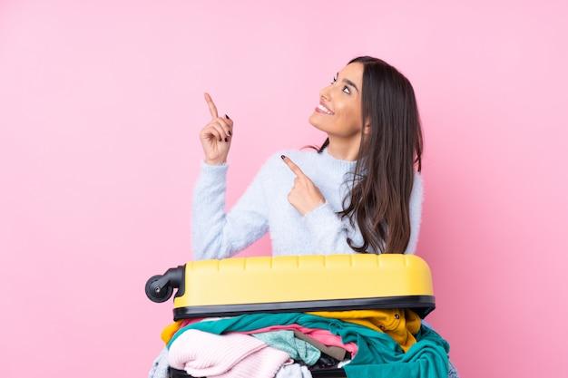 Mujer viajera con una maleta llena de ropa sobre rosa señalando con el dedo índice una gran idea
