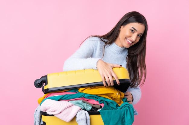 Mujer viajera con una maleta llena de ropa