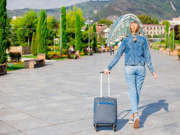 Mujer viajera con maleta mira el puente de la paz de tbilisi