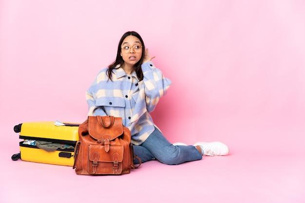 Mujer viajera con una maleta sentada en el suelo escuchando algo poniendo la mano en la oreja