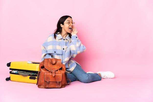 Mujer viajera con una maleta sentada en el suelo gritando con la boca abierta hacia un lado