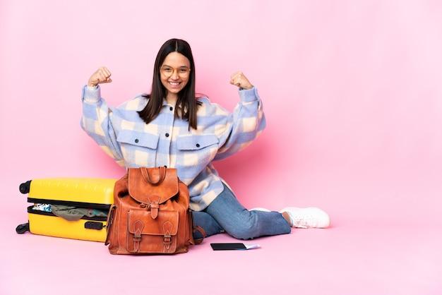 Mujer viajera con una maleta sentada en el suelo haciendo gesto fuerte